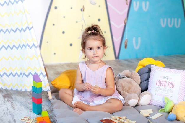 小さな女の子は、カラフルなキューブが付いている床で遊んでいます。赤ちゃんは子供部屋でおもちゃで遊ぶ。幼稚園で遊ぶ少女。子供の頃のコンセプト、子供の発達。ブロックで遊んで幸せな子。