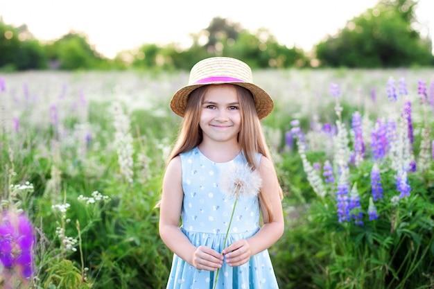 Красивая маленькая девочка в соломенной шляпе и платье держит одуванчик в цветущем поле. концепция природы. улыбающаяся девушка играет на летней лужайке. аллергия. детство. копировать пространство летняя радость