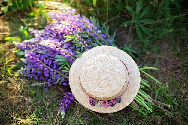 Фиолетовые цветы люпина покрыты соломенной шляпе в поле. шляпа возле букет цветов люпина на утренней траве. концепция летних пикников. соломенная шляпа украшена букетом цветов. декор в деревенском стиле