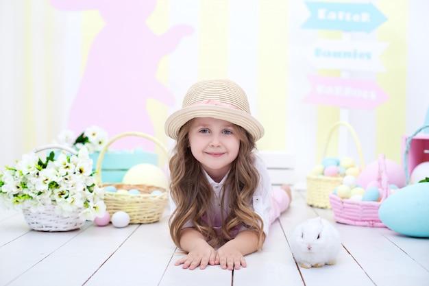 Милая маленькая девочка играет с пушистым белым кроликом