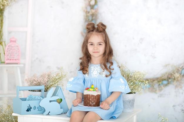 イースターケーキを手に白いテーブルに座っている笑顔の女の子