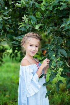 頭にピグテールを持つ少女は、リンゴ園で価値があります。子供は春の日に森の中を歩きます。夏休み。
