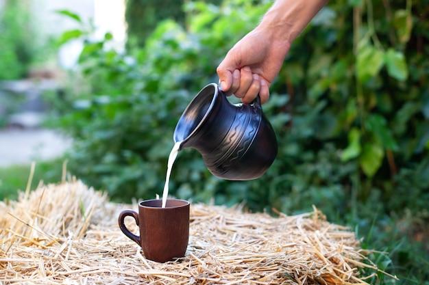 男の手は、フィールドの干し草の山の上のカップに粘土の水差しからミルクを流します。有機牛乳と素朴なスタイル。