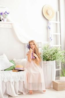 美しい笑顔の少女は、夏の花の花束が付いている寝室のベッドの上に座っています。ラベンダーの花束を保持している女の子。