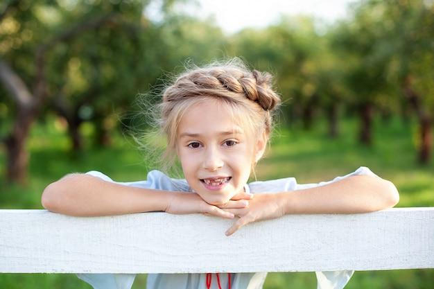 クローズアップの肖像画彼女の頭の周りのピグテールを持つ幸せな少女は、背景の庭に白い木製のフェンスに寄りかかった。