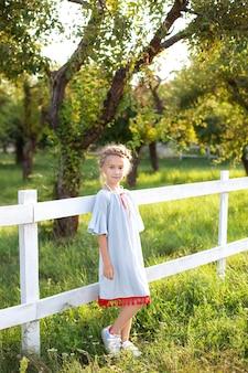庭の木製のフェンスゲートにピグテールと笑顔の女の子が立っています。