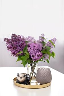 花瓶とテーブルの上の燭台にライラックの花の花束の横にあるウサギのウサギのセラミックの置物。