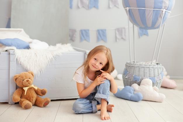 Улыбаясь маленькая блондинка играет в детской комнате с мишкой. ребенок в детском саду играет с игрушкой.