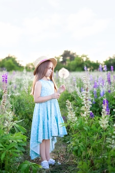 Красивая маленькая девочка в соломенной шляпе и платье держит одуванчик в цветущем поле. улыбающаяся девушка играет на летней лужайке.