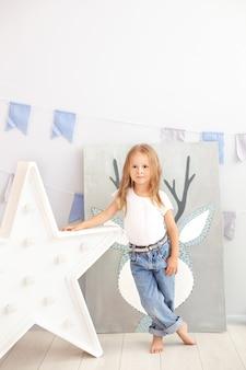 Маленькая девочка в джинсах и белой футболке стоит у светящейся звезды лампы. большая декоративная ретро звезда. рождество, новый год. большая звезда с лампочки на бетонную стену. скандинавский интерьер