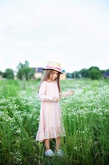 Красивая маленькая усмехаясь девушка в розовых платье и соломенной шляпе в поле маргариток. ребенок в поле цветущей ромашки летом.