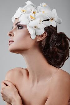 花を持つ美しい、魅力的な、官能的なブルネットモデルの肖像画
