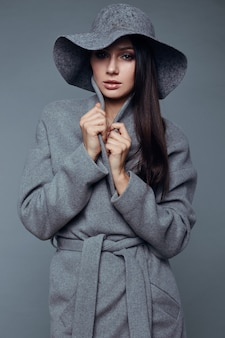 グレーのコートと帽子の若者のファッションブルネットの女性の美しさ
