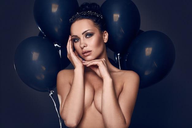 黒い風船を持つ美しいファッション裸モデルの女の子