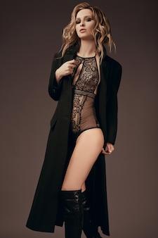 Сексуальная соблазнительная блондинка в нижнем белье и черном пальто