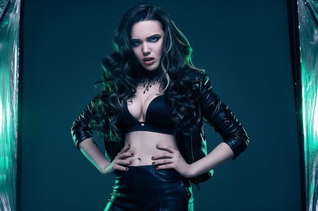 Молодая сексуальная девушка с длинными волосами в кожаной куртке