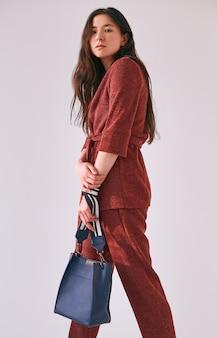 ファッショナブルな赤いスーツでエレガントなアジアの女性