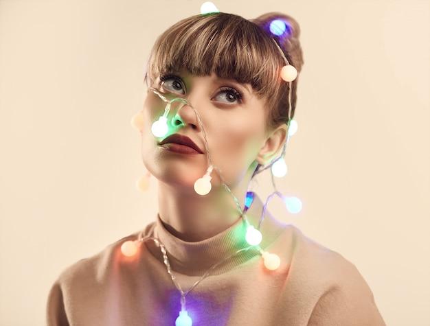 Красивая положительная белокурая женщина с рождественскими огнями на голове