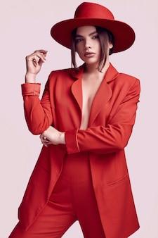 Элегантная красивая женщина в красном модном костюме и широкой шляпе