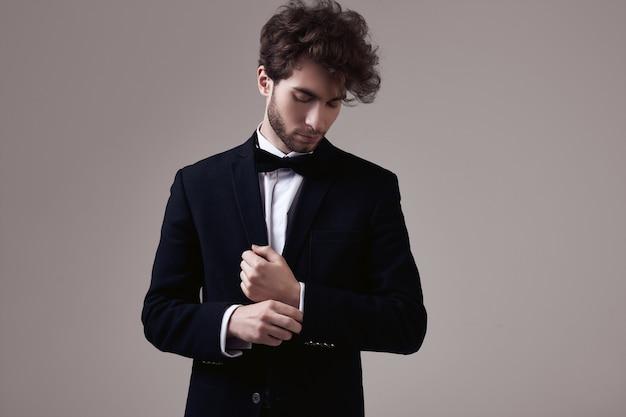 Красивый элегантный мужчина с вьющимися волосами в смокинге