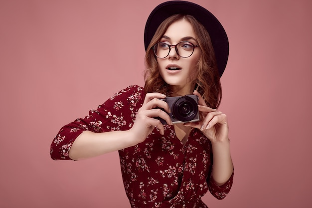 Элегантная хипстерская девушка в красном платье, черной шляпе и очках с камерой