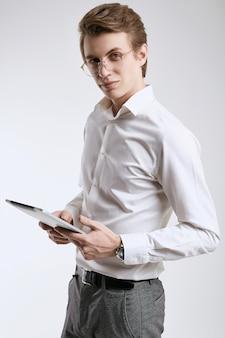 デジタルタブレットに取り組んでいるシャツで自信を持って若いビジネスマン