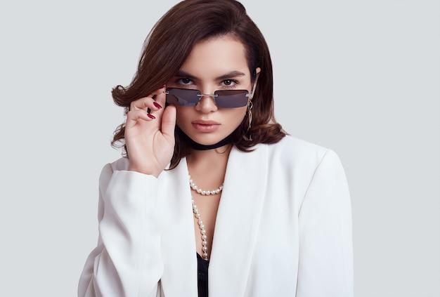 ファッションの白いスーツに黒髪の魅力的なエレガントな女性