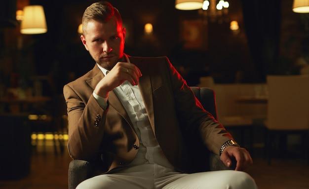 レストランでポーズをとってスーツを着ている思いやりのあるハンサムな実業家