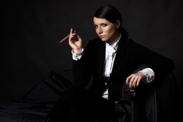 Красивая молодая брюнетка женщина с сигаретой в костюме
