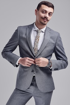 Портрет красивого молодого уверенно арабского бизнесмена с причудливыми усами в моде серый полный костюм на студии