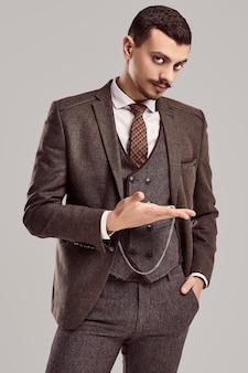 ウールの茶色の完全なスーツで派手な口ひげを持つハンサムな若い自信を持ってアラビア語ビジネスマンの肖像画はスタジオでアンティーク時計を保持します