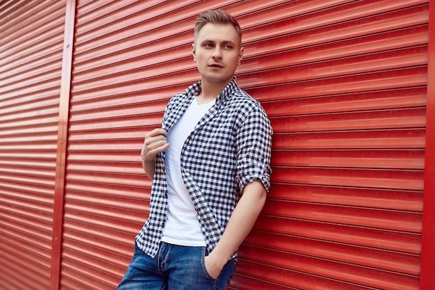 Молодой красавец в рубашке и джинсах возле красных ворот