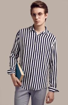 Молодой человек в полосатой рубашке позирует с книгой на сером фоне