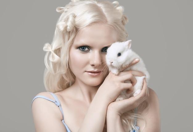 Блондинка-альбинос в элегантном платье позирует с милым маленьким кроликом