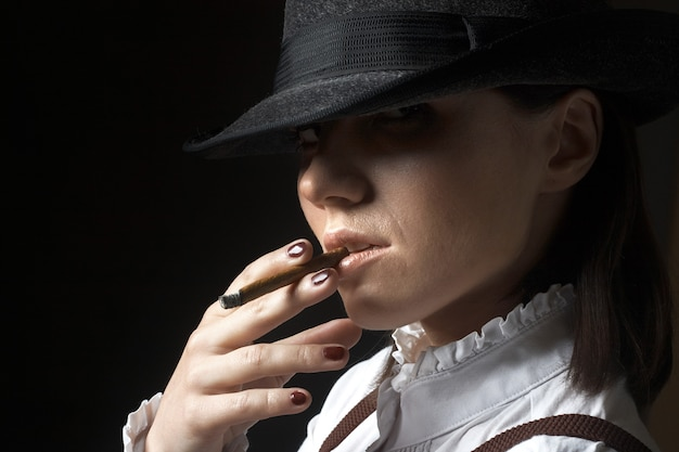 Красивая сексуальная брюнетка женщина в шляпе курить сигарета