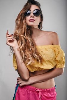 スタイリッシュな美しい女性のスタジオ明るい夏ファッションポートレート