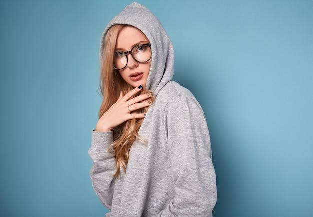 灰色のパーカーとメガネでかわいい肯定的なブロンドの女性