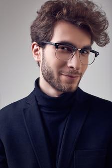 スーツとメガネを着て巻き毛を持つハンサムなエレガントな男