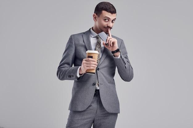ファッショングレーのスーツに口ひげを持つハンサムな若いアラビア語ビジネスマン