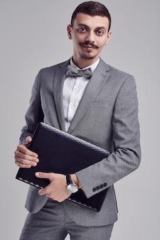 グレーのスーツで口ひげを持つハンサムな若いアラビア語ビジネスマンはラップトップを保持します