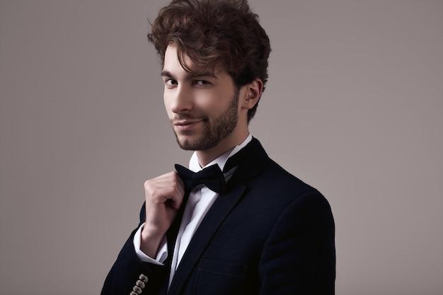 タキシードを着て巻き毛を持つハンサムなエレガントな男