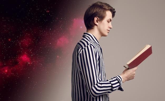 灰色の背景で本を読んでストライプシャツの若いハンサムな男