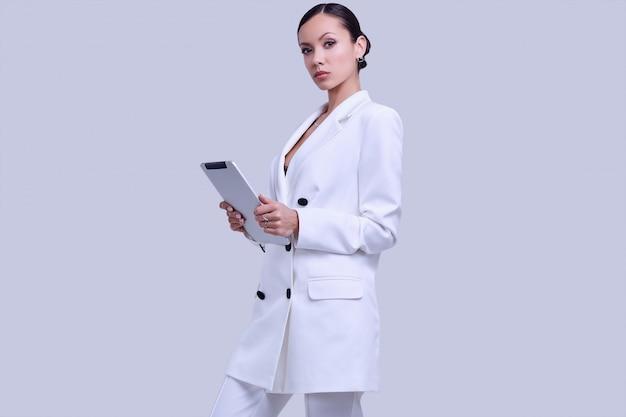 デジタルタブレットでファッションの白いスーツでゴージャスなラテン女性