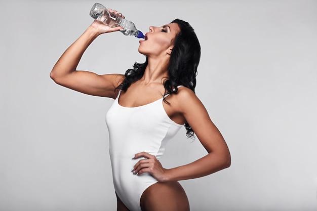 Портрет молодой женщины фитнеса в теле с бутылкой
