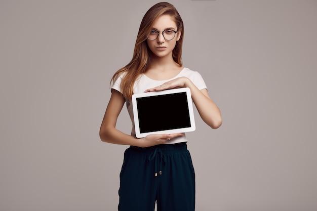 Милая девушка в белой рубашке и очках, держа цифровой планшет