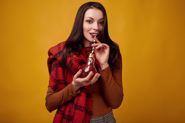 Красивая брюнетка с большим красным вязаным шарфом пьет горячий чай