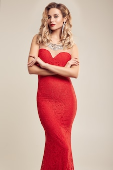 ファッションの赤いドレスを着て豪華なエレガントなブロンドの女性