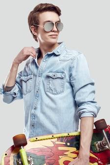 Хипстерский человек в солнцезащитных очках и джинсовой куртке позирует со скейтбордом