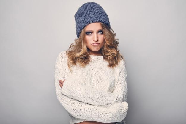 Портрет красивой белокурой женщины в белом свитере