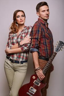 ファッショングラマーギターとスタイリッシュな流行に敏感な若いカップルの肖像画